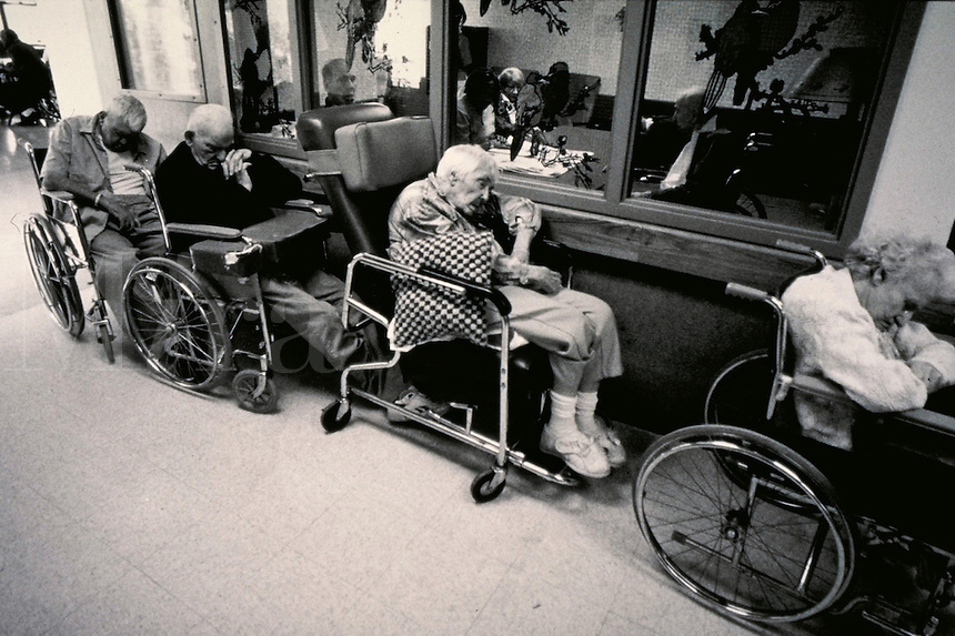 HANDICAPPED  WHEELCHAIR SENIOR CITIZENS IN THE CORRIDOR OF A HEALTH CARE FACILITY