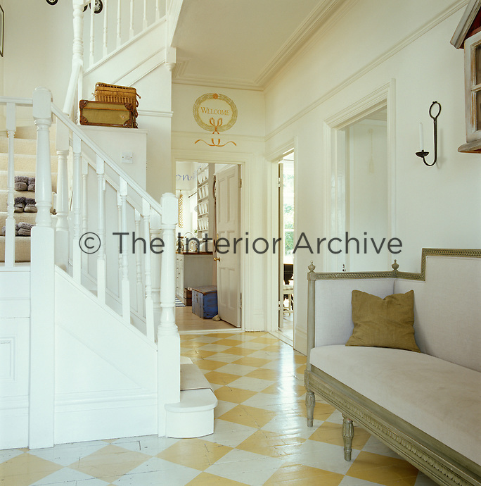 The wooden floor of this hallway has been hand- painted in a yellow and white harlequin pattern