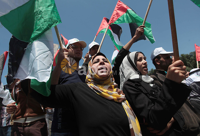 Palestinians hold placards and Palestine flags during a demonstration to calling for an end in the political division and the national reconciliation in Gaza city, on April 22, 2014. A delegation representing the PLO is expected to arrive in Gaza on Tuesday evening for reconciliation meetings with Hamas, a Fatah spokesman said. Photo by Ashraf Amra