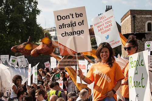 A demonstrator holds a placard which says 'Don't Be Afraid Of Change' as she marches in front of the Houses of Parliament during the Climate Change demonstration, London, 21st September 2014. © Sue Cunningham