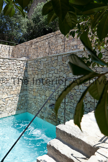 A wall of natural stone surrounds the outdoor swimming pool in this courtyard garden