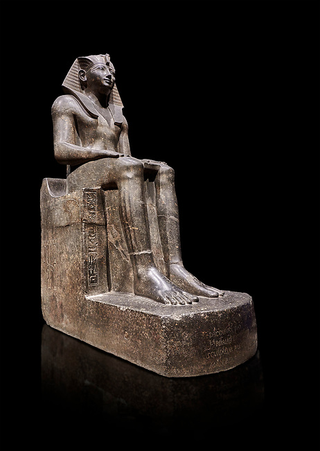 Ancient Egyptian statue of Tuthmosis II, granodorite, New Kingdom, 18th Dynasty, (1479-1425 BC), Karnak, Temple of Amun. Egyptian Museum, Turin. black background.<br /> <br /> Tuthmosis II is shown wearing Royal regalia including the shendyt kilt, the nemes headdress and the uraeus cobra on his forehead. Between his legs in a bulls tail, the symbol of power. On the sides of the throne is the sema-tawy, a sign composed of a lotus and papyrus, the symbols od Upper and Lower Egypt. Under the feet of the king are the Nine Bows, the enemies of Egypt. Together these symbolise that the pharaoh keeps the two halves of Egypt together and protects them against her enemies. Drovetti Collection. C 1376