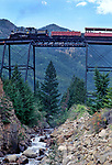 Georgetown Railroad train glides over high bridge leaving Georgetown, Colorado