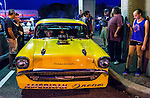 Bellmore, New York, USA. 7th August 2015. Groups of people are at yellow 1957 Chevrolet muscle car, with a blower (supercharger air compressor) sticking out through hole in hood, and American Dream written under the front grill, and parked under the elevated train tracks at the Friday Night Car Show held at the Bellmore Long Island Railroad Station Parking Lot. Hundreds of classic, antique, and custom cars were on view at the free weekly show, sponsored by the Chamber of Commerce of the Bellmores.