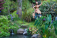 "Whimsical art statue ""The Gift"" by Vicki Jo Sowell as focal point by pond with grasses in Sherry Merciari California garden"