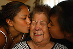 Chumash Elder, Eva Pagaling, 80, recieves birthday kisses from grandaughters; Jenna Pagaling,17, left, and Eva Pagaling,13, at family gathering for her 80th birthday at family home on reservation in Santa Ynez Valley, August 2004.
