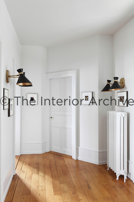 Retro lights are mounted to spotlight photographs hanging in this spacious hallway with wood flooring and white walls.