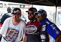 Sept. 28, 2012; Madison, IL, USA: NHRA top fuel dragster drivers (R-L) Antron Brown and Shawn Langdon pose for a picture with a fan at an autograph session during qualifying for the Midwest Nationals at Gateway Motorsports Park. Mandatory Credit: Mark J. Rebilas-