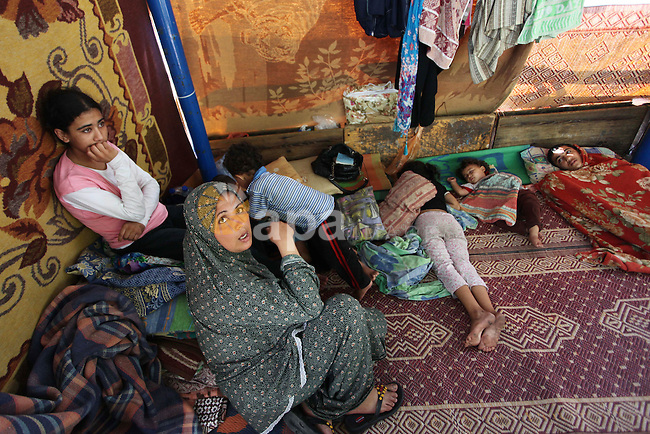 "Palestinians sit at a UN school at the Jabalia refugee camp in the northern Gaza Strip after the area was hit by Israeli shelling on July 30, 2014. Israeli bombardments early on July 30 killed ""dozens"" of Palestinians in Gaza, including at least 16 at a UN school, medics said, on day 23 of the Israel-Hamas conflict. Photo by Ashraf Amra"