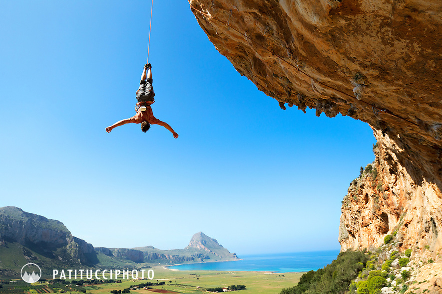 Climber lowering off a very steep climb upside down. San Vito lo Capo, Sicily