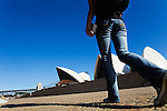 A backpacker walks toward the Sydney Opera House  Sydney, New South Wales, AUSTRALIA.