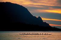 An outrigger canoe team paddles against a beautiful sunset at Makana point, Kauai.
