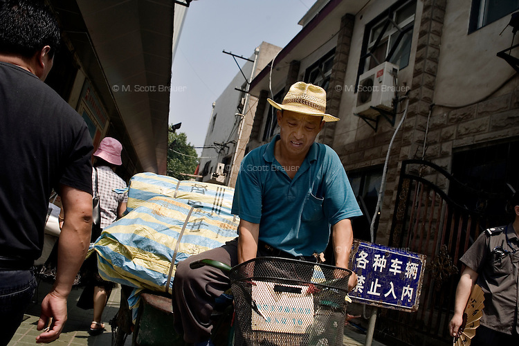 A market seller carries goods through a market on his bike in Nanjing, Jiangsu, China.