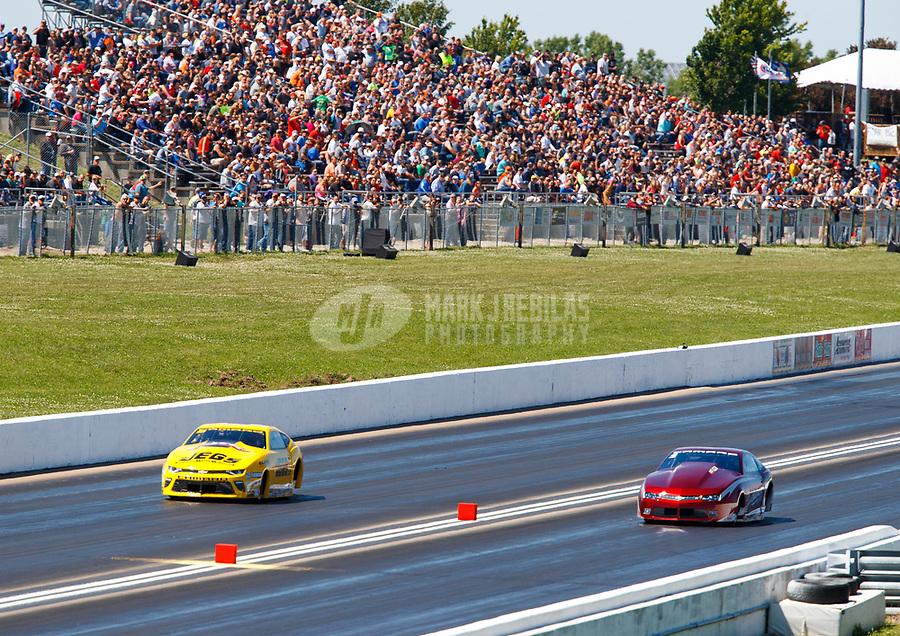 May 21, 2017; Topeka, KS, USA; NHRA pro stock driver Jeg Coughlin Jr (left) races alongside Bo Butner during the Heartland Nationals at Heartland Park Topeka. Mandatory Credit: Mark J. Rebilas-USA TODAY Sports
