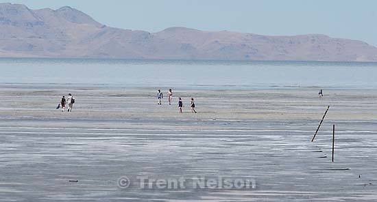 Braving the summer heat and the smell of the Great Salt Lake, people make their way to and from the distant shoreline. Thursday afternoon near Saltair. 08/07/2003<br />