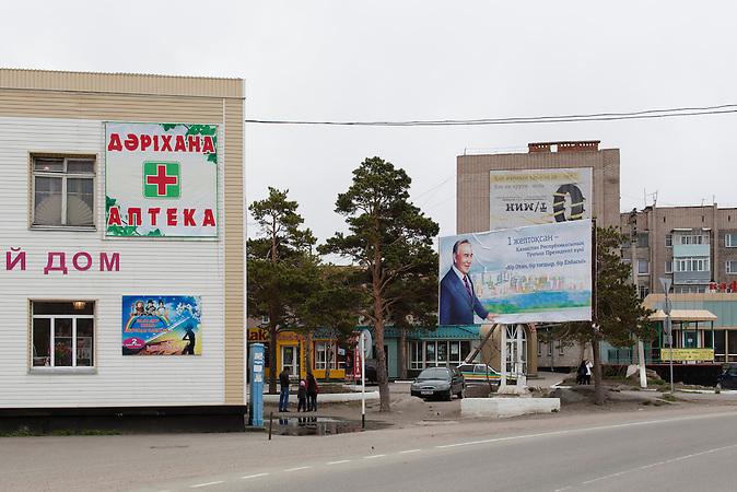 """Plakat in Burabai. Das Gebiet in der Provinz Akmola gilt als Perle Kasachstans und wird oft als """"Kasachische Schweiz"""" bezeichnet. An einem großen idyllischen See gelegen, ist Burabai ein Rückzugsort für die Superreichen des zentralasiatischen Steppenstaates. Auch der Präsident soll eine eigene Villa am See beistzen, schwer bewacht und für die Untertanen nicht einsehbar. Kasachstan ist rohstoffreich und prosperiert. Kritik an den Schattenseiten des Aufstiegs duldet das System von Präsident Nursultan Nasarbajew nur geringfügig. Bilder von Hinterhöfen und grauen Vorstädten sollen nicht an die Öffentlichkeit gelangen. / Kazakhstan is a resource-rich and prosperous country.  President Nursultan Nasarbajew's system hardly allows any criticism. Pictures of backyards and suburbs are not supposed to go public."""