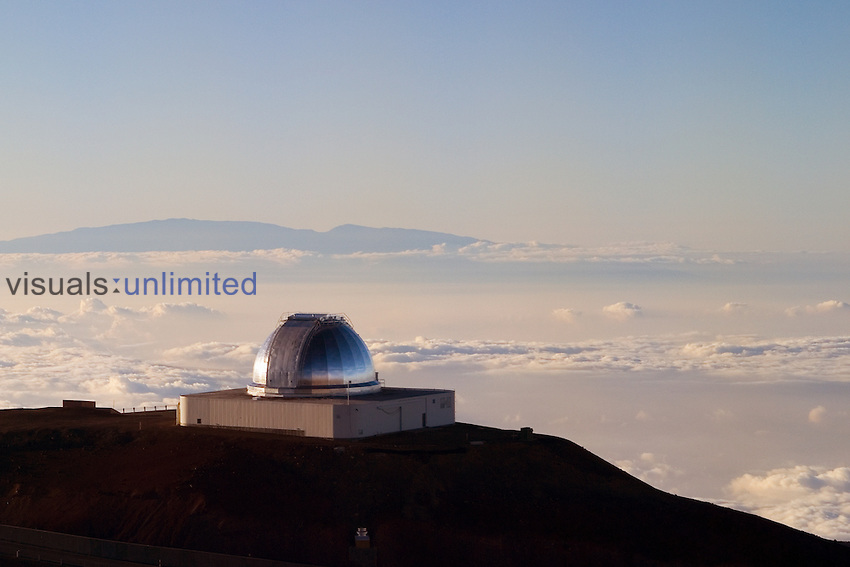 NASA Infrared Telescope Facility or IRTF of Mauna Kea Observatories, and silhouette of Haleakala of Maui at distance, Big Island, Hawaii.