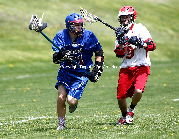 Litchfield, CT- 10 May 2014-051014CM16-  St. Paul's Joe Strid attempts to move the ball away from their goal as Wamogo's Tony DiLeo tries to make the stop from behind  during their lacrosse matchup in Litchfield on Saturday.  Christopher Massa Republican-American