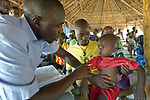 Nurse Ezuma Rhone examines a child in an outreach clinic in the Rhino Refugee Camp in northern Uganda. As of April 2017, the camp held almost 87,000 refugees from South Sudan, and more people were arriving daily. About 1.8 million people have fled South Sudan since civil war broke out there at the end of 2013. About 900,000 have sought refuge in Uganda. <br /> <br /> The clinic was sponsored by Global Refuge International, which receives support from the Global Health Program of The United Methodist Church. <br /> <br /> Because of the nature of the Rhino Camp, where refugees are spread out over a wide area, it's not possible for many of them to access health care, so Global Refuge International holds outreach clinics on a regular basis through several areas of the camp.