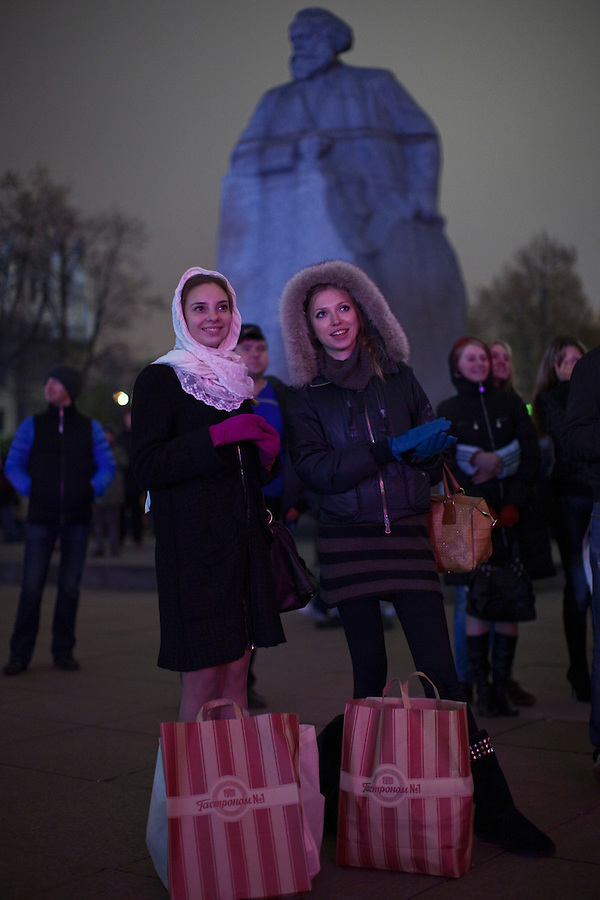 Moscow, Russia, 28/10/2011..Two woman with their shopping watch the gala reopening of the Bolshoi Theatre on giant video screens erected in Ploschad Revolutsii opposite the theatre, which had been closed since 2005 for reconstruction work that cost some $700 million.