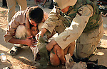 Army medics with the 1st Cavalry Division operating in support of the Marines of Scout-Sniper platoon 1st BN 4th Marines assist Iraqi civilians severely wounded by mortars fired by fighters from the Moqtada al-Sadr-led Mehdi Army during the Battle of Najaf on August 19, 2004. The child died.<br />