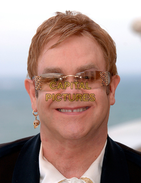 "SIR ELTON JOHN .Photocall for ""It's a Boy Girl Thing"" by.Rocket Films (owned by Elton John).59th International Cannes Film Festival, France,.20 May 2006..Ref: FIN.portrait headshot gold skull earring glasses.www.capitalpictures.com.sales@capitalpictures.com.©Steve Finn/Capital Pictures"