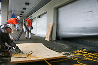 From left, Kevin Pelletier, Rob Wilson, and Joe Killmade, all of Bam Contracting, prepare boards to cover the broken windows in the main terminal of Lambert- St. Louis International Airport on April 23, 2011. Storms last night damaged both the interior and exterior of the airport. The airport was closed all day today and officials hope to reopen tomorrow. REUTERS/Sarah Conard (UNITED STATES)