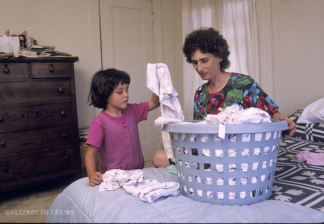 Oakland, CA Mother supervising daughter's (age four) work sorting laundry at home