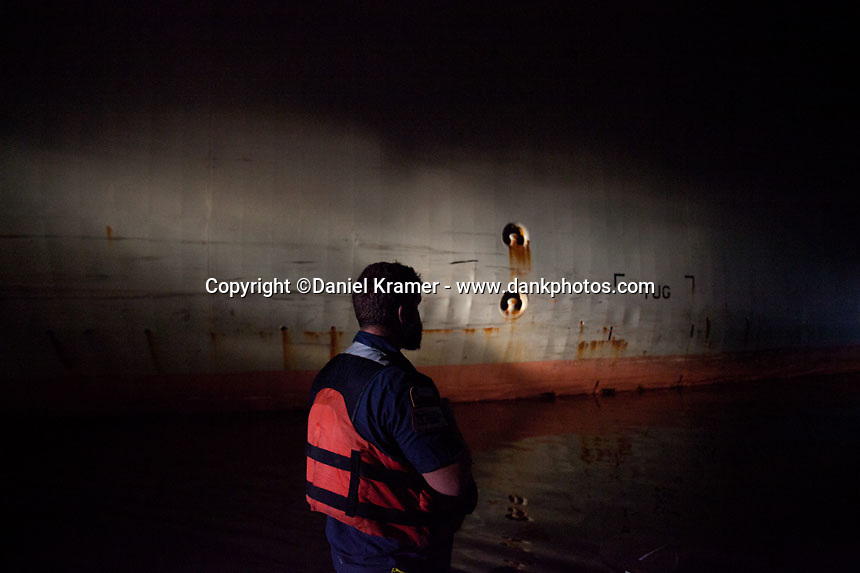 With the side of the Oregon Highway lit by the pushboat's spotlight, Buffalo Marine tankerman Terry Curow prepares to lash the barge to the ship on Friday, Nov. 11, 2016.
