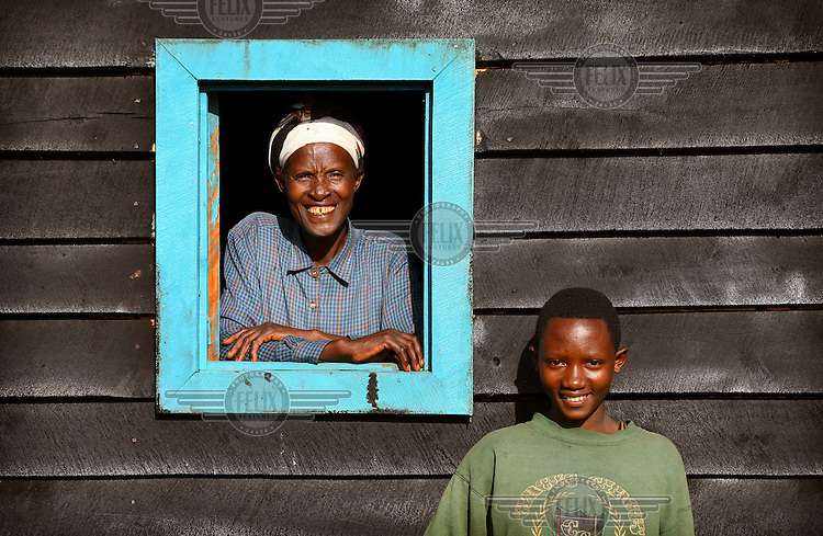 Valerie, who lost her husband and eight children in the 1994 genocide, stands at the window of her new home that was built by Rwanda Aid.