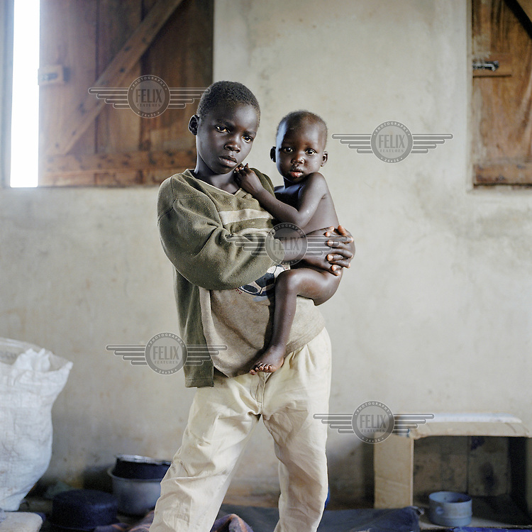 """Wiliam Otoa (10) holding his 2 year old brother Innocent in the feeding centre run by MSF (Medecins Sans Frontieres). They are orphans. Wiliam is a former LRA (Lord's Resistance Army) abductee. He was forced by the LRA to kill two of his best friends. After 2 years he was left nearly dying of exhaustion. He managed to return to Agweng camp where he found his family again. Less than 3 months later the LRA attacked and brutally murdered his parents who were working in the fields close to Agweng. William is severely traumatized by these events and has been  transferred to a special programme for former child soldiers. His young brother is looked after by a relative.   .For 18 years the LRA rebels have terrorised the Northern provinces of Uganda abducting 20,000 children and forcing 1.6 million people to flee their homes. According to Medecins Sans Frontieres (MSF) the mortality rate among children in some areas is five times the rate internationally agreed to constitute an 'emergency out of control'. The UN's under-secretary general for humanitarian affairs has called Northern Uganda the """"largest neglected humanitarian emergency in the world""""."""