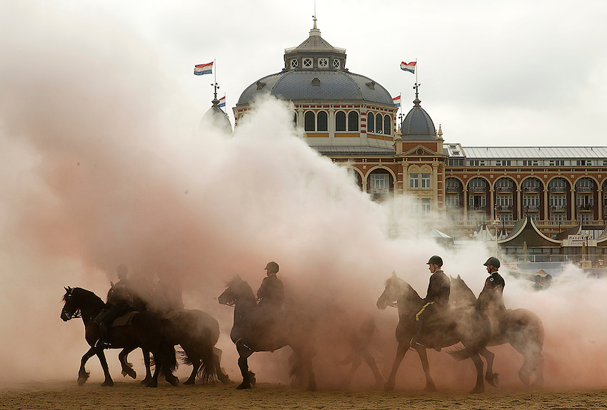 Members of the Dutch Royal guard of honour rehearse in front of the Kurhaus hotel ahead of the Dutch 2011 budget presentation by guiding their horses through smoke and gunfire on the beach at Scheveningen September 20, 2010. Dutch Queen Beatrix will present the budget in The Hague on September 21, 2010. REUTERS/Michael Kooren ( NETHERLANDS) ..
