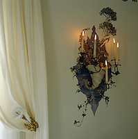 In the Duchess of Windsor's bathroom a candle sconce in the shape of trailing ivy is given a matching setting in a clever twist of trompe l'oeil
