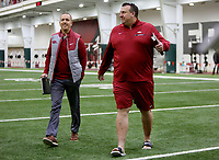 NWA Democrat-Gazette/DAVID GOTTSCHALK  Head coach Bret Bielema (right) arrives to speak with the media Wednesday, March 15, 2017, before the Arkansas Pro Day inside the Walker Pavilion on the campus of the University of Arkansas in Fayetteville.