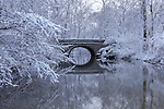Snow covered trees framing a stone bridge reflected in the mirror - like river water during winter In the park, Sharon Woods, Southwestern Ohio, USA