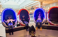 Visitors to the Queens Center Mall in the borough of Queens in New York onSaturday, December 17,  2016 wear virtual reality goggles and sit in rocking pods as they watch a virtual reality video.  (© Richard B. Levine)