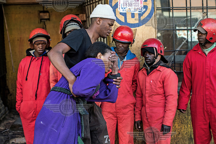 Catherine Mathebula breaks down as her son Kenny escorts her from the so-called 'hijacked building' where they lived on Bree Street after being evicted by the Red Ants.The Red Ants are a controversial private security company often hired to clear squatters from land and so-called 'hijacked' properties.
