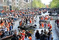 Koningsdag in Amsterdam. De grachten kleuren oranje. Boten op de prinsengrach