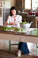 Portrait of chef Maddalena Caruso shelling the bountiful harvest of peas from her vegetable garden