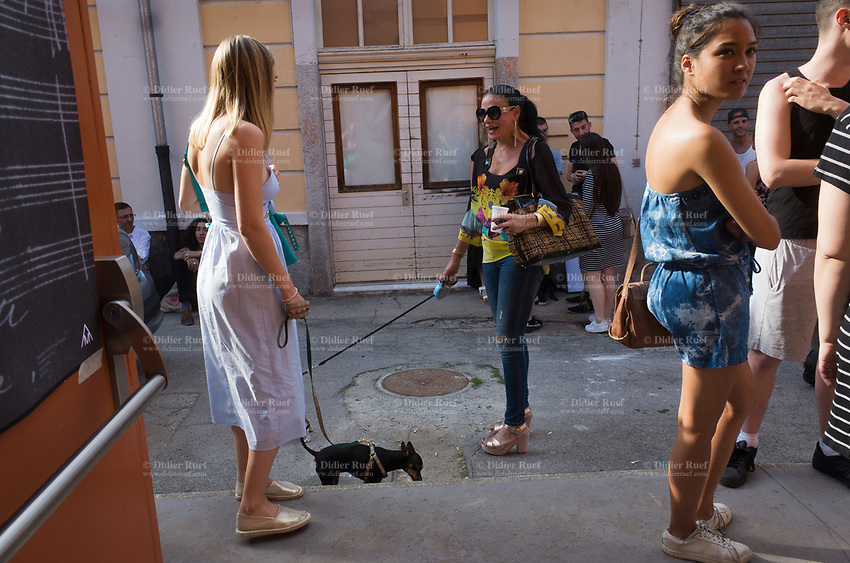 Switzerland. Canton Ticino. Lugano. Opening of CSIA students' exhibition at the Ex Macello. A group of students from the Centro scolastico per le industrie artistiche (CSIA) stand outside in the courtyard. A fashionable woman wearing high heels shoes holds a tiny dog on a leash. 3.06.2017 © 2017 Didier Ruef