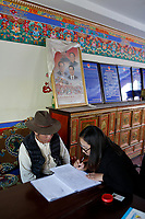 Lhasa, Tibet, China - A Tibetan man enrols his child for free classes at a community centre in Lhasa, September 2018.