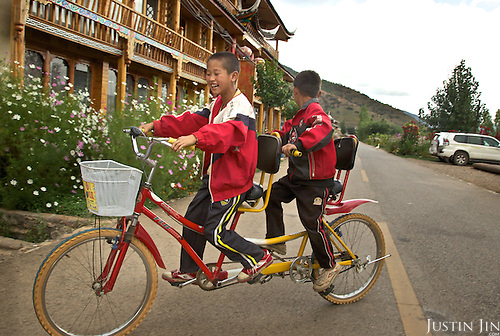 Boys ride on a tandem bicycle in Lugu Hu Lake in Sichuan province.