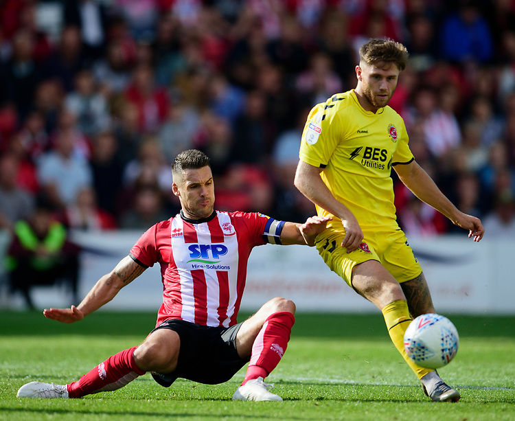 Fleetwood Town's Ched Evans is tackled by Lincoln City's Jason Shackell<br /> <br /> Photographer Andrew Vaughan/CameraSport<br /> <br /> The EFL Sky Bet League One - Lincoln City v Fleetwood Town - Saturday 31st August 2019 - Sincil Bank - Lincoln<br /> <br /> World Copyright © 2019 CameraSport. All rights reserved. 43 Linden Ave. Countesthorpe. Leicester. England. LE8 5PG - Tel: +44 (0) 116 277 4147 - admin@camerasport.com - www.camerasport.com