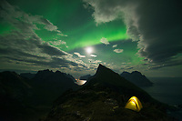 Northern lights shine in sky over tent, Moskenesøy, Lofoten Islands, Norway