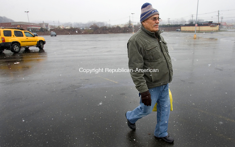 WATERBURY, CT. 27 November 2012-112712SV05-Herberto Fleicianno of Waterbury walks home after grocery shopping during a snowstorm on Wolcott Street in Waterbury Tuesday..Steven Valenti Republican-American