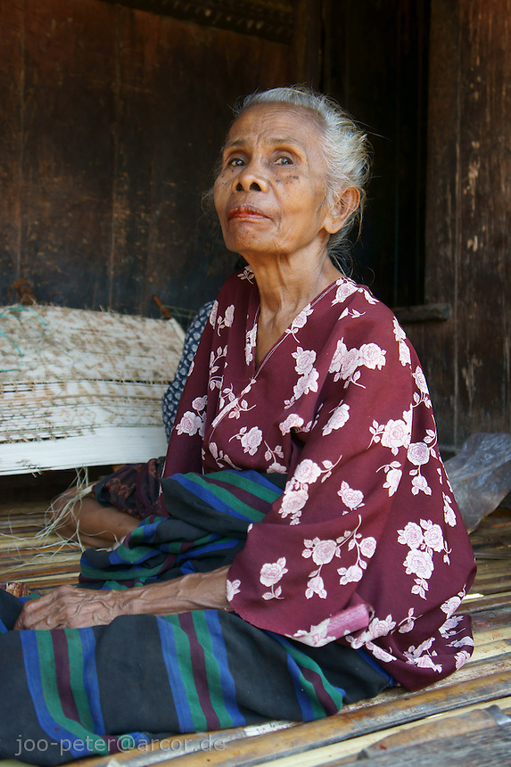 woman on veranda of her house  in Wolotopo, famous traditional village near coastal city Ende, island  Flores in archipelago of Indonesia