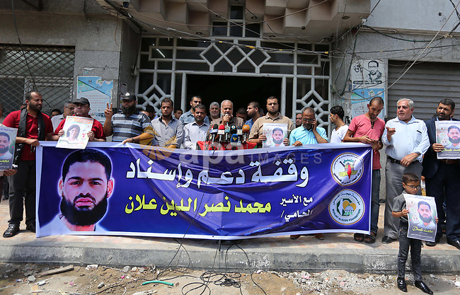 Palestinian supporters of the Islamic Jihad Movement, hold placards during a protest to show solidarity with Palestinian prisoners held in Israeli Jails, in Gaza city, on July 5, 2017. Photo by Ashraf Amra