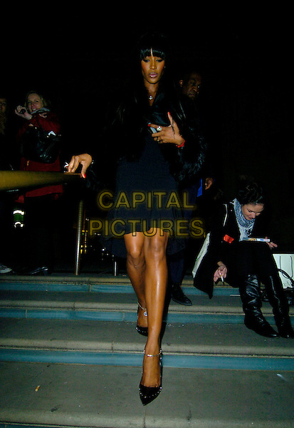 NAOMI CAMPBELL.Kulture2Couture: By Design.launch party at V&A Museum, London, England.16th November 2007.Kulture 2 Couture full length black fur jacket coat shoes dress fringe silver anklets clutch bag purse walking down steps.CAP/CAN.©Can Nguyen/Capital Pictures