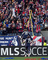 New England Revolution forward Zack Schilawski (15) leaps the boards as he celebrates his goal. In a Major League Soccer (MLS) match, the New England Revolution defeated DC United, 2-1, at Gillette Stadium on March 26, 2011.
