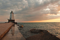 Ludington Michigan's Pierhead Lighthouse sits in front of the sunsetting through the clouds over Lake Michigan